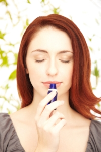Close-up of a relaxed woman with a bottle of scented oil